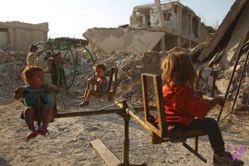 Trẻ em chơi trong một đường phố bị phá hủy trong chiến tranh ở thị trấn Douma