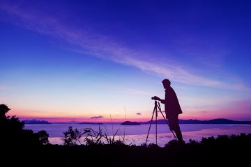 Silhouette young photography man take a photo in sunrise or sunset beautiful scenery Enjoying on the hill