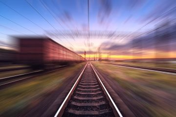 Railway station with cargo wagons in motion at sunset. Railroad with motion blur effect. Railway platform at dusk. Heavy industry. Conceptual background