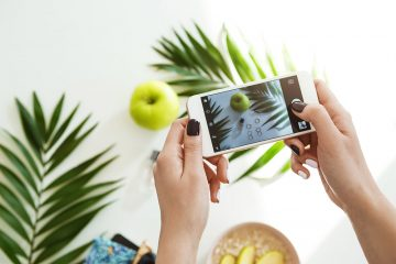 Hand holding smartphone touching screen and taking cool stylish photos for social network on table.
